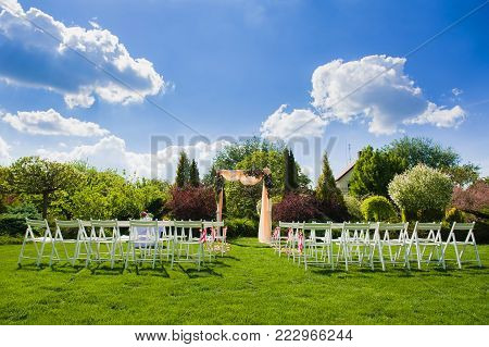Lanscape full vertical view of wedding reception for marriage ceremony with flower decoration. White chairs in front of beautiful wedding arch with peach color fabric on nature background.