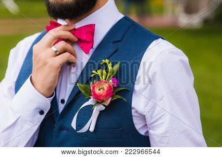 Handsome man, bridegroom close up with pink bow and boutonniere outdoor