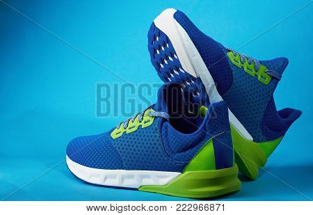 Shop display of new sneakers shoes isolated on blue background. Blue colorful running shoes