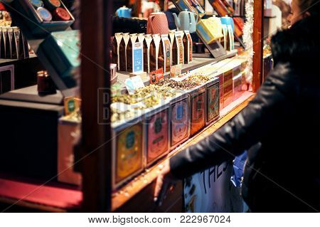 STRASBOURG, FRANCE - DEC 23, 2016: Woman shopping for organic tea at the Christmas market in Strasbourg during winter holidays