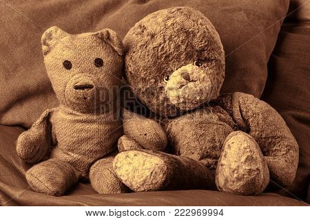 Grandparents vintage teddy bear lovers. Old-aged toy. Cute happy married couple sitting holding hands very much in love. Sepia toned valentines day or anniversary image.