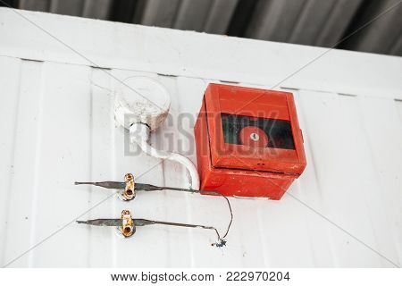 Alarm setting on the wall with two steel pipes and red cage with key button