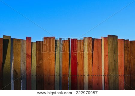 Multicolored wooden wall and blue sky. A colored wall of wood with a lot of copy space. Wooden fence and blue sky. Colored Painted Old Shabby Wooden Desk Background. Wooden Background.