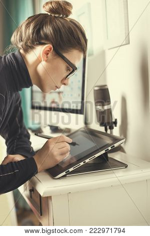 young woman working: Drawing, photography and retouching on a computer laptop using a digital tablet and stylus pen.