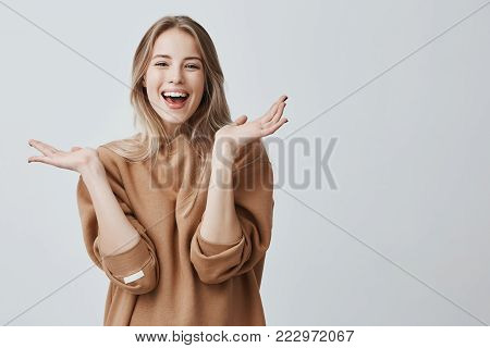 Pretty beautiful woman with blonde long hair looking at camera having excited and happy facial expression, clapping with her hands against blank studio wall, expressing her excitement with present
