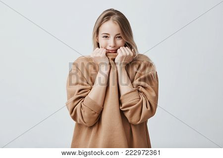Studio shot of good-looking beautiful girl smiling, pleased to hear compliments, isolated against gray studio background. Pretty female with fair straight hair and dark appealing eyes hiding her face in warm loose sweater, being shy