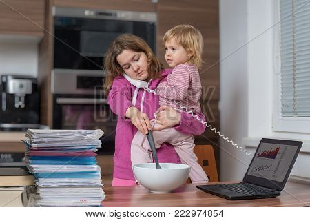 Multitasking mother is babysitting and working at home.