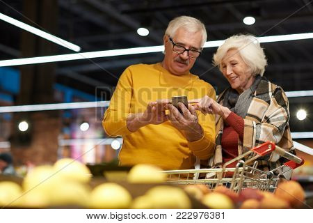 Portrait of cheerful senior couple grocery shopping in supermarket, using smartphone to read shopping list and calculate prices while standing by fruits and vegetables isle, copy space
