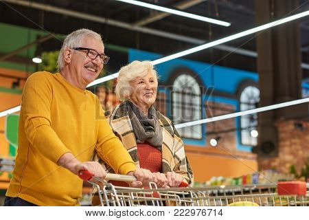 Portrait of cheerful senior couple grocery shopping in supermarket pulling shopping cart together and smiling happily, copy space