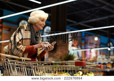 Side view portrait of elegant senior lady grocery shopping in supermarket, using smartphone to read shopping list and calculate prices while leaning on shopping cart, copy space