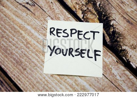 Respect Yourself -Hand written yellow sticky note wooden background