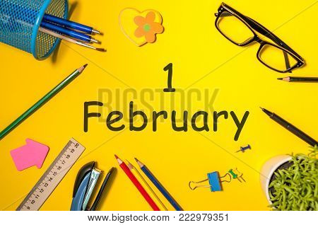 February 1st. Day 1 of february month, calendar on student or some manager workplace, yellow background. Winter time.