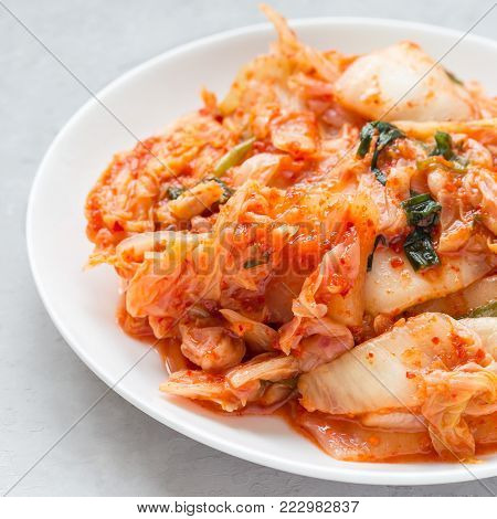 Kimchi cabbage. Korean appetizer on a white plate, square format