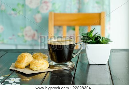 Breakfast, cup of hot coffee and vanilla choux cream on wooden table for eating in the morning