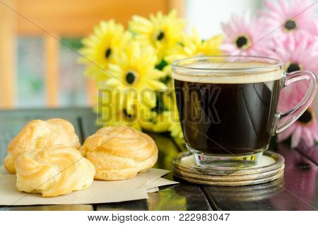 Breakfast, Cup of hot coffee and vanilla choux cream on wooden table for eating