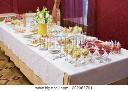 food, celebration, party concept. on the white tablecloth there are different snacks and salads in the glasses for wine, among them there are martini glasses with red drinks