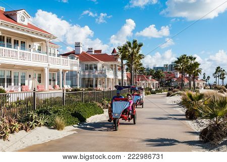 CORONADO, CALIFORNIA - JANUARY 20, 2018:  People pedal on surrey bikes past the Hotel del Coronado, a historic beachfront hotel built in 1888, and formerly the largest resort hotel in the world.