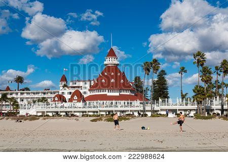 CORONADO, CALIFORNIA - JANUARY 20, 2018:  People enjoy Coronado Central Beach near the Hotel del Coronado, a historic beachfront hotel built in 1888 and formerly the largest resort hotel in the world.