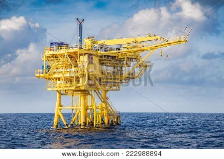 Offshore oil and gas industry, well head remote platform where produced raw gas and crude oil for sent to central processing platform, surface tools of well service worker on deck.