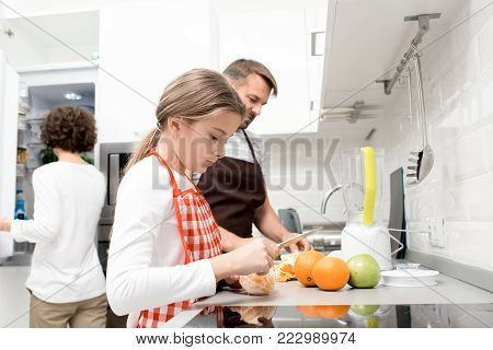 Profile view of pretty little girl wearing apron cutting oranges while helping her middle-aged father and curly mother to prepare healthy breakfast, interior of modern kitchen on background