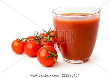Ripe red tomatoes and tomato juice in a glass on white background, isolated. Closeup.