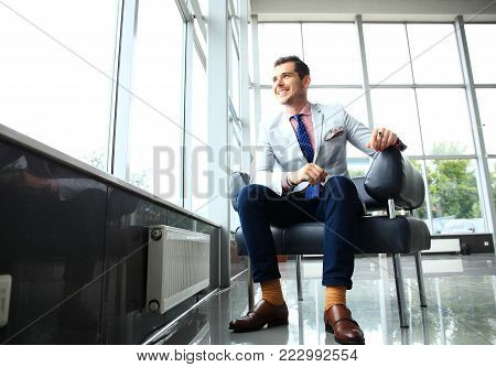 Low angle shot of a handsome young businessman in a stylish modern office space with large windows relaxing on a couch in a business lounge