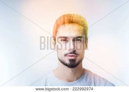 Enigmatical bearded man keeping smile on his face while wrinkling forehead while looking at camera