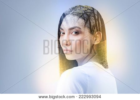 Serious model turning head and pressing lips while posing on camera
