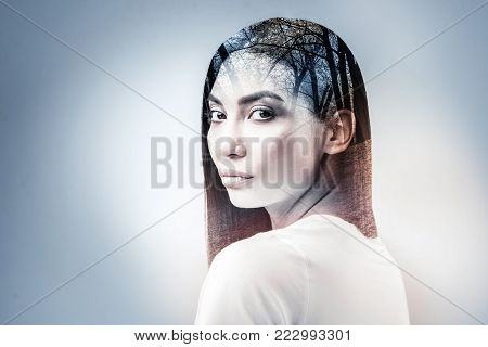 Attractive model pressing lips and turning head while being in studio