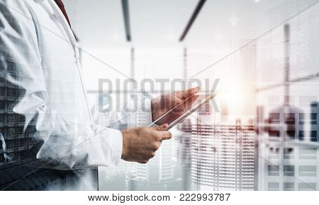 Double exposure of confident doctor in white sterile coat standing inside hospital office and modern cityscape view on background. Concept of modern medical industry