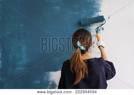 Young asian happy woman painting interior wall with paint roller in new house