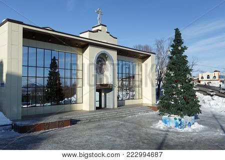 PETROPAVLOVSK CITY, KAMCHATKA, RUSSIA - JAN 6, 2018: Diocesan Spiritual and Enlightenment Center of Petropavlovsk, Kamchatka Diocese of Russian Orthodox Church and Christmas tree in front of building