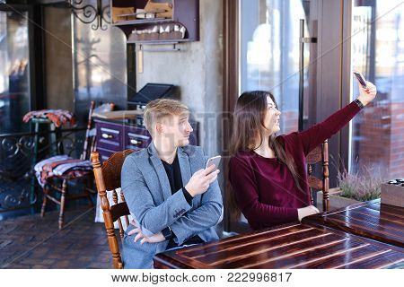 Physicist with smartwatch on hand in cafe with colleague taking selfies using smartphone wait friend, irritated guy checking social networks watching smiling Asian girl. Young people sitting near table in cozy coffee house