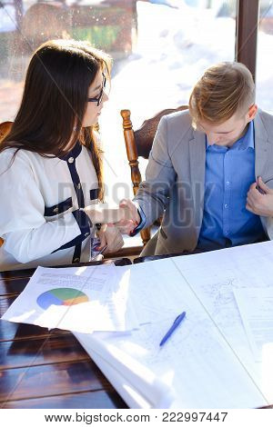Female student enjoying and proving boy rightness on smartphone in drawing architectural project. Guy and girl working with drawing task at cafe. Concept of drafting at catering establishment.