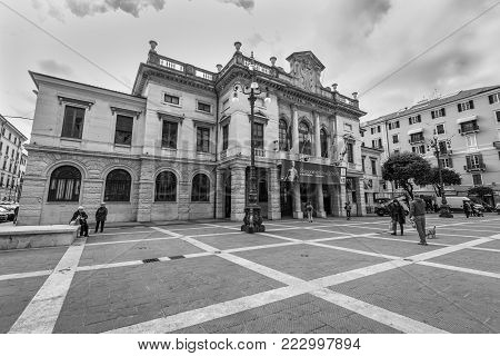 Savona, Italy - December 2, 2016: People rest and walk in front of the Palace of the Municipality of Savona (Palazzo Comune di Savona) in Savona, Liguria, Italy. Black and white photography.