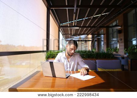 Inventory strategist solving problems and using laptop at cafe table. Clever hardworking man dressed in white shirt working with papers. Concept of  analyzing model forecast  to design contingency plans and catalog displays to make successful, consumer re