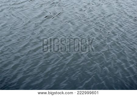 The texture of the water in the river under the influence of wind. A lot of shallow waves on the water surface