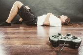 Addiction and dependency concept. Young man with pad joystick playing games. Male addicted to console playstation videogames. poster