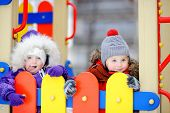 Little boy and girl in winter clothes having fun on outdoors playground. Active outdoors leisure with children in winter. Kid during stroll in a snowy winter park poster