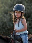 very little girl on her black horse with sport helmet poster