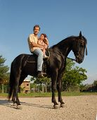riding father and little girl on a black horse poster