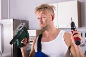 Portrait Of A Young Workman With Dirty Face Holding Electric Drill And Screwdriver In Kitchen poster