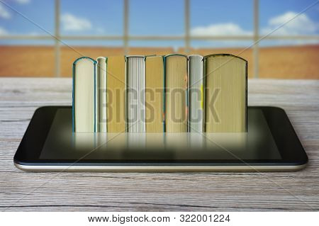 Ebook Concept. Some Books With Ebook Reader Or Tablet Pc On A Wooden Table.