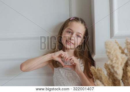 Beautiful Little Girl Shows With Gestures I Love You.a Girl Shows Love.cute Girl In A White Dress Sh