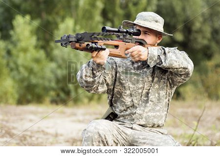 The Young Army Soldier Or Hunter Is Aiming And Shooting With Crossbow Weapon Outdoors.