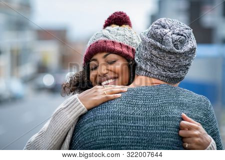 Happy african american girlfriend hugging boyfriend on street with closed eyes. Friends meeting and embracing outdoor. Romantic multiethnic young couple embracing in winter clothes in the city.