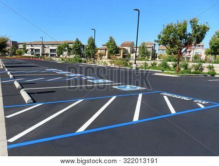 Freshly resurfaced and repainted handicap parking space in a parking lot. The number of handicap spaces increases with the size of the lot, requiring roughly one handicapped spot per 25 spaces. poster