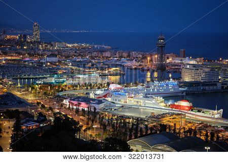 BARCELONA, SPAIN - APRIL 15, 2019: Aerial view of Barcelona city skyline with city traffic and port with yachts and ferry ships illuminated in the night. Barcelona, Spain