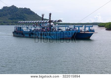 KOH PHANGAN, THAILAND - AUGUST 31, 2013: Blue ferry boat conveying passengers and cars to Koh Phangan island port.