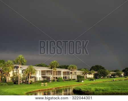 residential area on green landscape over rainy sky with rainbow in Florida